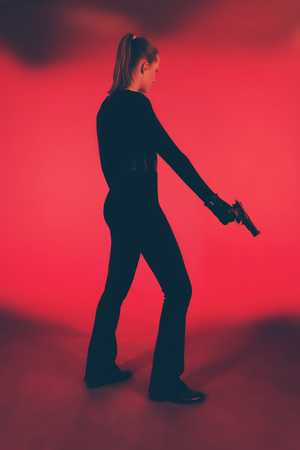Silhouette of woman in black holding pistol. Against red background.