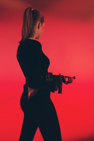 Young woman standing with machine gun against red background. Stock Photo