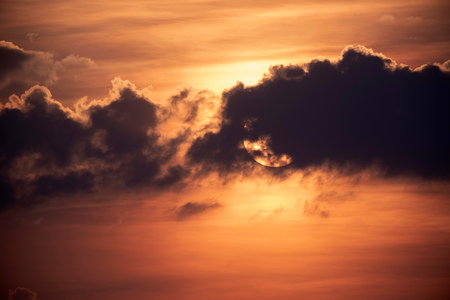 Cloudy sunset with sun behind cloud. Stock Photo