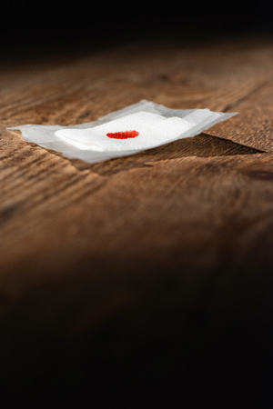 Used bandage with blood spot fallen on wooden floor.
