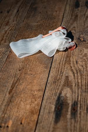 Bandage with tape fallen on wooden floor. Standard-Bild - 121676192