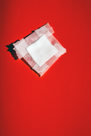 Bandage gauze with tape fallen on red floor. Top view.