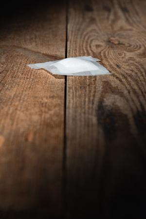 Used bandage fallen on wooden floor in strip of light. Stock Photo