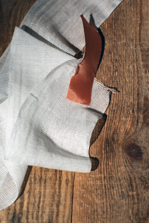 Used bandage with tape fallen on wooden floor. Top view. Standard-Bild - 121676212