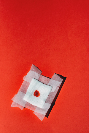Bandage gauze with blood on red background. Top view.