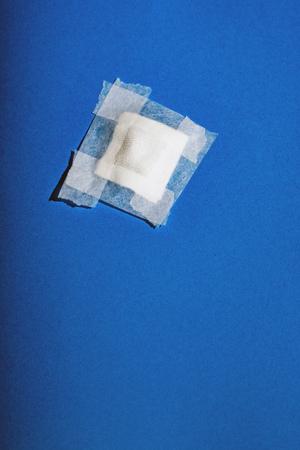 Bandage with tape fallen on blue floor. Top view. Standard-Bild - 121676240