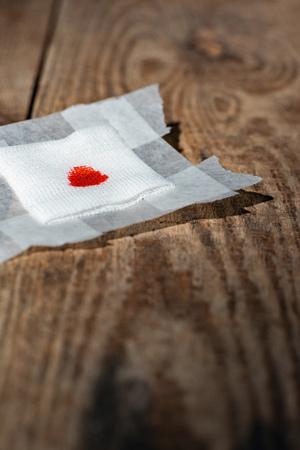 Used bandage with blood on wooden floor. Standard-Bild - 121676251