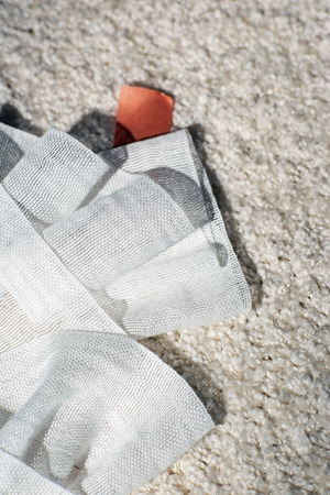 Used bandage fallen on white carpet. Top view. Stock Photo