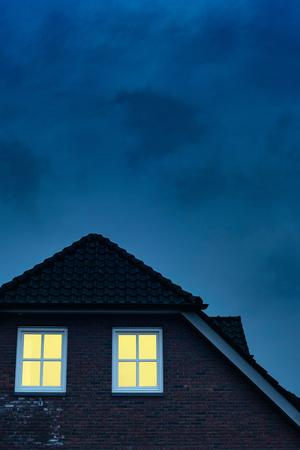 Landhaus mit beleuchteten Fenstern in der Dämmerung. Standard-Bild
