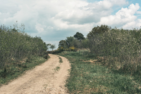 Dirt road uphill in cloudy countryside.