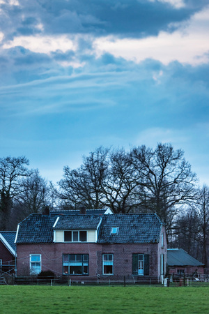 Old farmhouse in dutch countryside with bare trees and cloudy sky. Stock Photo