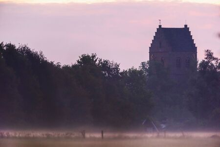 Historical church in misty countryside. Stockfoto