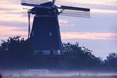 Dutch windmill in misty countryside. Stockfoto