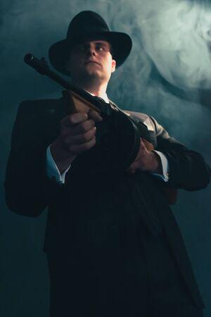 Gangster rétro au chapeau dans la nuit brumeuse tire avec une mitrailleuse. Banque d'images