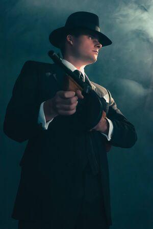 Gangster rétro se dresse avec mitrailleuse dans la brume.