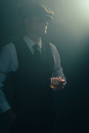 Retro businessman with cap holds glass of whiskey in smoky room.