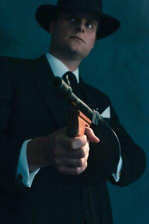 Retro gangster in hat shoots with machine gun.