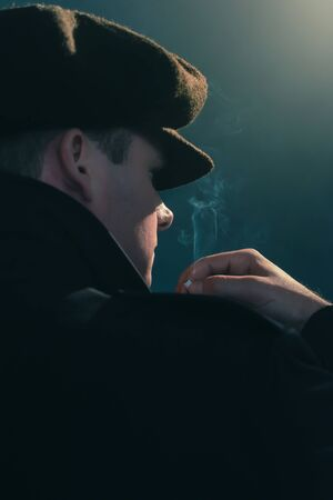 Retro man with cap smokes cigarette in smoky room. Side view.
