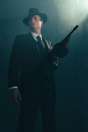 Gangster rétro se dresse avec mitrailleuse en fumée.