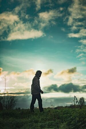 Mysterious man in rural landscape with cloudy sky at sunset.