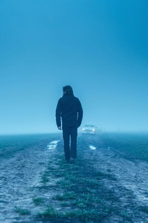 Man in black jacket and trousers with classic car on muddy country road in the mist. Stock Photo