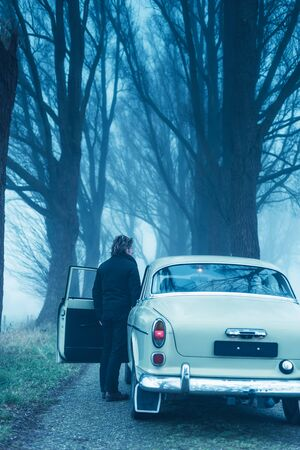 Man in black jacket and trousers standing at door of classic car on misty country road. Stock Photo