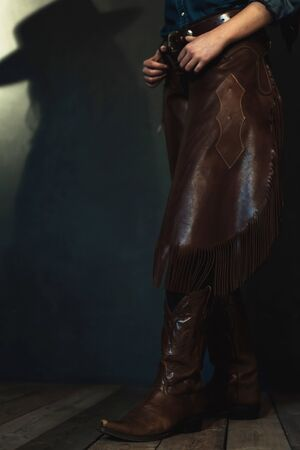 Leather boots and chaps of cowgirl.