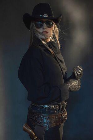 Blonde cowgirl in black hat wearing dark sunglasses.