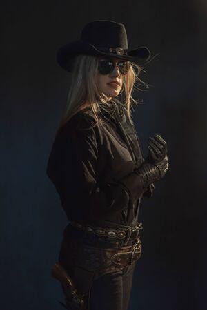 Blonde cowgirl in black hat wearing dark sunglasses. Stock Photo