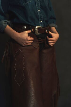 Blonde cowgirl with brown leather chaps and jeans shirt.