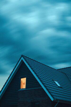 Burglar with handgun in ominous house with illuminated window under stormy sky at dusk.