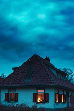 Creepy house with illuminated windows under stormy sky at twilight.