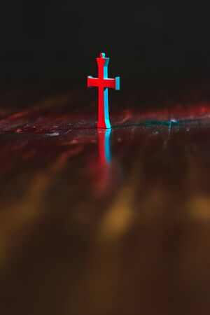 Old little crucifix on wooden table in red and blue light at night.