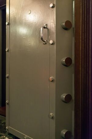Opened old-fashioned solid vault door of a bank.