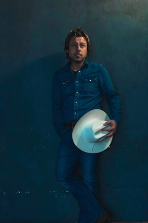 Man wearing denim shirt holding cowboy hat in hand standing by wall.