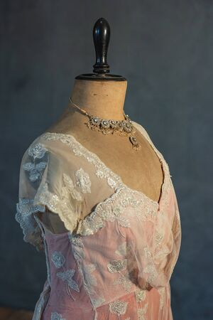 Shimmering necklace on vintage mannequin bust with pink victorian dress. Side view. Фото со стока