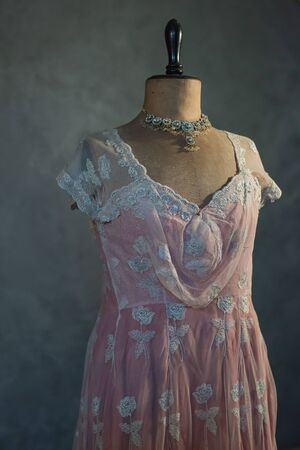 Shimmering necklace on vintage mannequin bust with pink victorian dress.