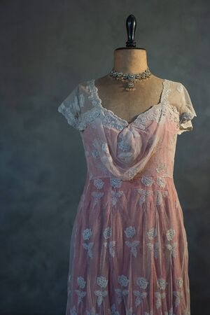Pink victorian dress on vintage mannequin bust against grey wall. Фото со стока