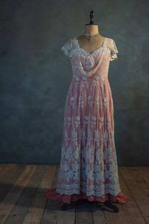 Pink victorian dress on vintage mannequin bust in empty room.
