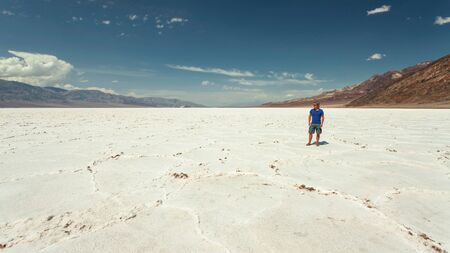 Man standing on salt flatsin sunny desert.