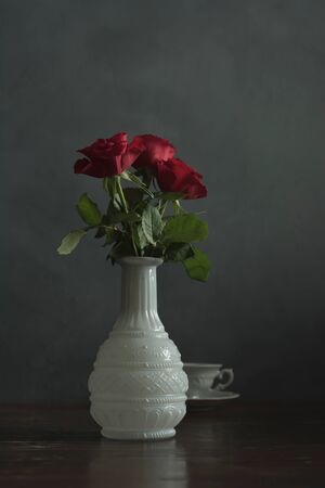 Antique white vase with red roses and china cup on wooden table. Stockfoto