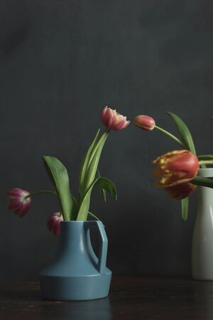 Blue vintage vase with pink tulips on wooden table.