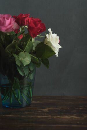 Vase with red, pink and white roses on a wooden table.