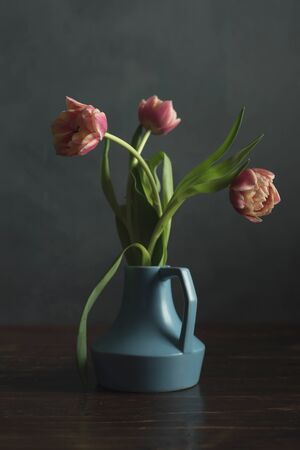 Vintage blue vase with pink tulips on wooden table.