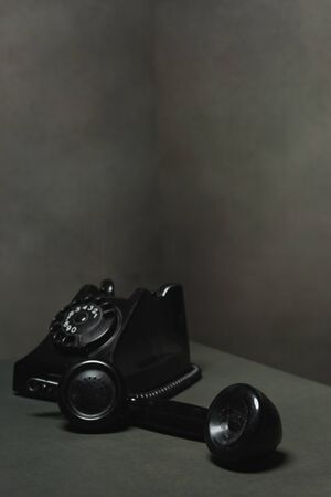 Vintage black telephone with receiver next to it in gray empty space.