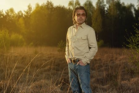 Man in shirt and sunglasses in nature at sunrise during spring. Stok Fotoğraf