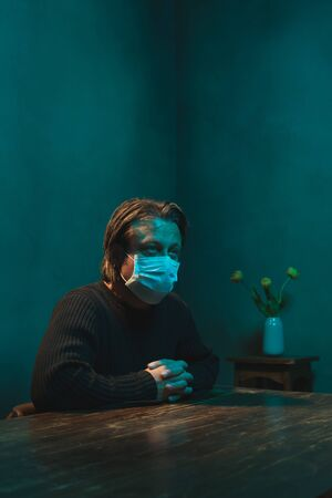 Man with hygienic mask sits in room behind table in the night.