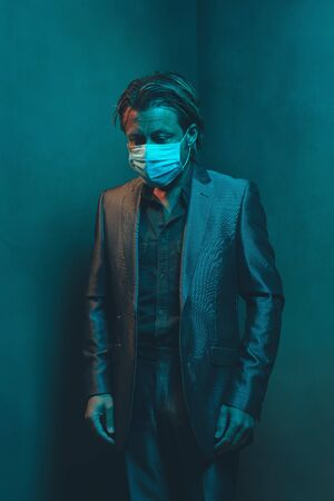 Man with surgical face mask in suit stands in corner of empty room. Banco de Imagens