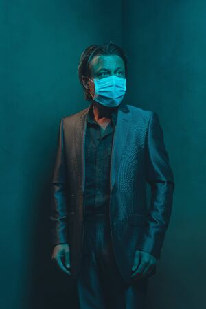 Man with surgical face mask in suit stands in corner of empty room.