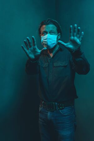 Man with surgical face mask in green shirt and jeans stands in corner of empty room. Making holding distance gesture with hands. Banco de Imagens